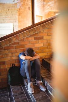 Retrato de colegial sosteniendo tableta digital y libro junto a la escalera