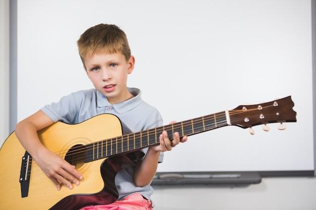 Retrato de colegial tocando la guitarra en el aula
