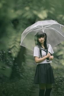 Retrato de colegiala asiática caminando con paraguas en la pasarela de la naturaleza en lluvia