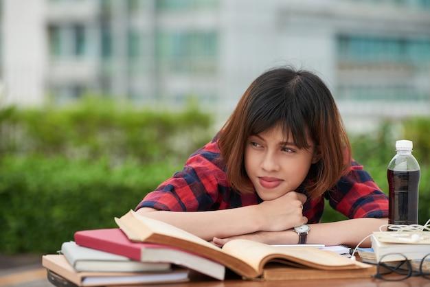 Retrato de colegiala cansada de la rutina de hometask descansando en una mesa llena de libros