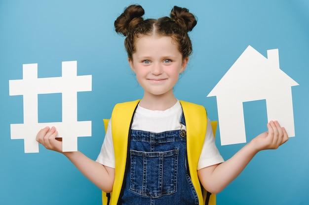Retrato de colegiala feliz tiene signo de hashtag blanco y modelo de casa, etiqueta para negocios, lleva mochila amarilla, aislada sobre fondo azul. monitoreo de redes sociales, medición de medios, escuela.
