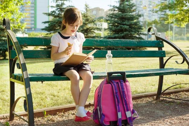 Retrato de colegiala leyendo libro, comiendo helado