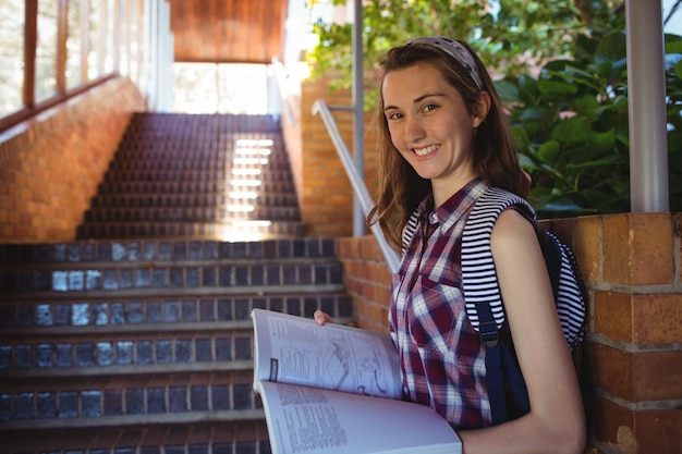 Retrato de colegiala leyendo libro junto a la escalera
