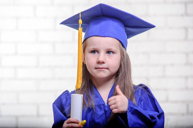 Retrato de colegiala linda con sombrero de graduación en el aula
