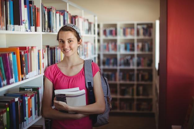 Retrato de colegiala de pie con libros en la biblioteca