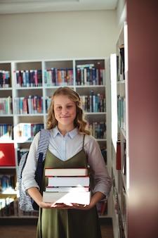Retrato de colegiala de pie con una pila de libros en la biblioteca