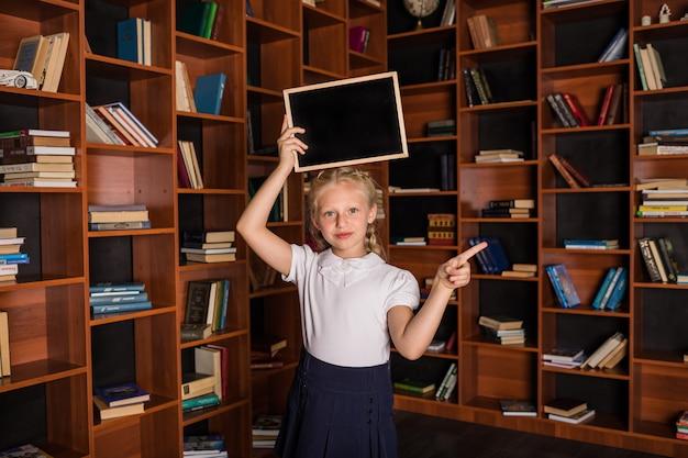 Retrato de una colegiala rubia en uniforme con una pizarra apuntando hacia el lado
