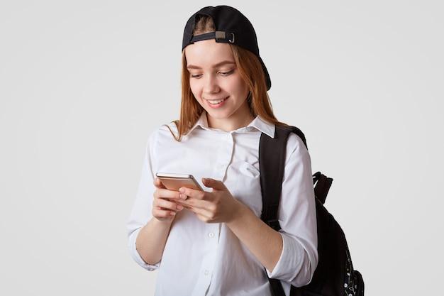 Retrato de colegiala satisfecha juega en línea en un teléfono inteligente durante el descanso en la escuela
