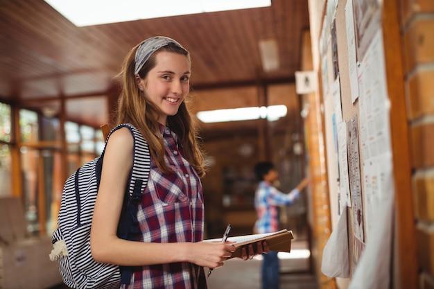 Retrato de colegiala sonriente de pie con el libro cerca del tablón de anuncios en el corredor