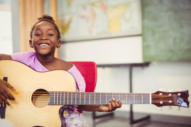 Retrato de colegiala sonriente tocando la guitarra en el aula