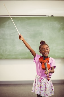 Retrato de colegiala sonriente tocando el violín en el aula