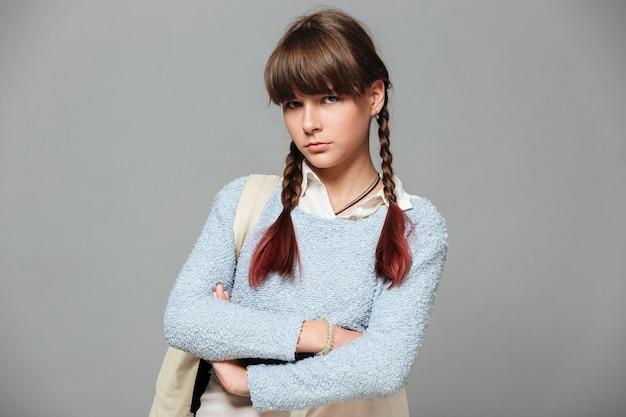 Retrato de una colegiala triste molesta de pie con los brazos cruzados