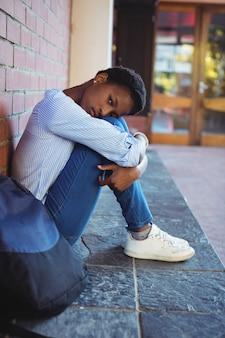 Retrato de colegiala triste sentado contra la pared de ladrillo