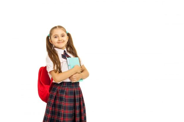 Retrato de una colegiala en uniforme de pie sobre fondo blanco.