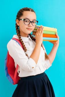 Retrato de una colegiala en vasos con libros de texto en azul amarillo