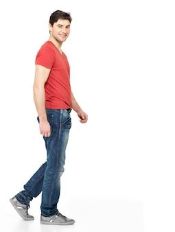 Retrato completo del hombre que camina sonriente en casuals de la camiseta roja aislado en el fondo blanco.
