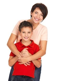 Retrato completo de una joven madre feliz con su hijo de 8 años sobre la pared blanca