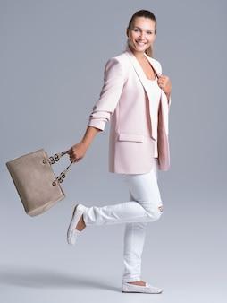 Retrato completo de una mujer joven feliz con bolso posando en el estudio.
