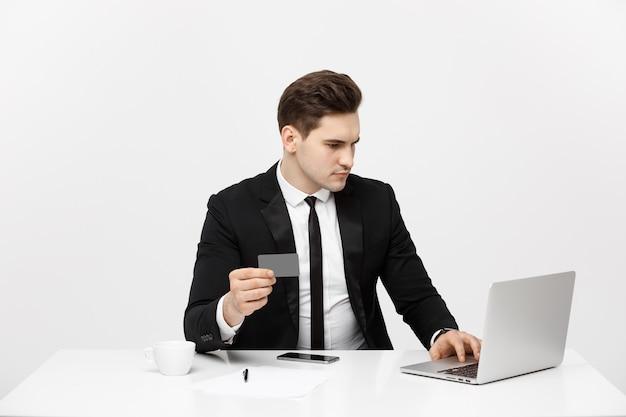Retrato de concepto de negocio de joven empresario usando computadora portátil y teléfono móvil con tarjeta de débito ...