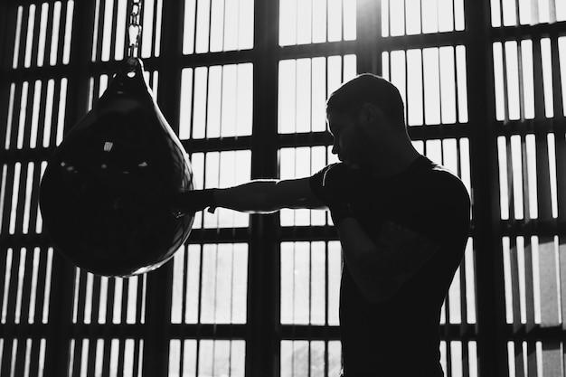 Retrato conceptual de un brutal boxeador tatuado que entrena en el ring y golpea un saco de boxeo