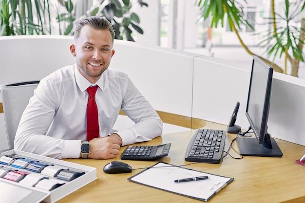 Retrato del concesionario de automóviles caucásico sonriente sentado en la mesa