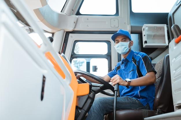 Retrato de conductor de autobús asiático vistiendo uniforme y máscara