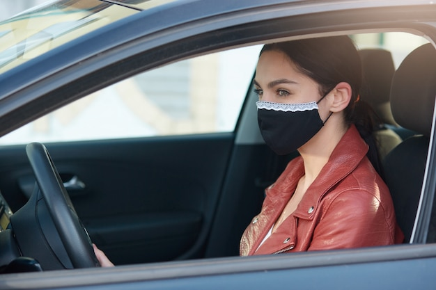 Retrato de un conductor experimentado y cuidadoso mirando a un lado, conduciendo un automóvil, usando una máscara antibacteriana para protección de covid19, cumpliendo con las reglas. concepto de coronavirus.
