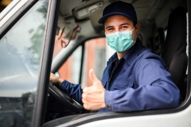 Retrato de un conductor de furgoneta dando pulgares arriba y con una máscara, el concepto de coronavirus