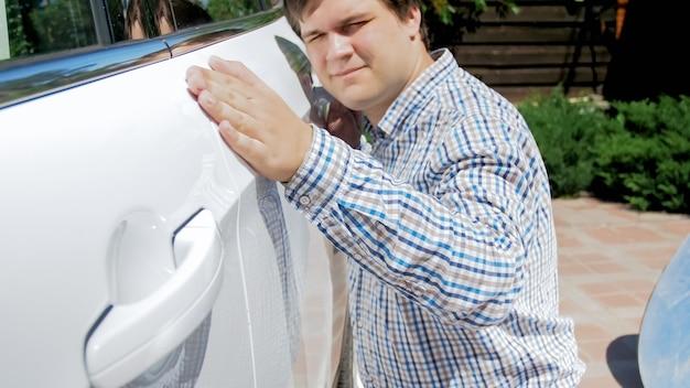 Retrato del conductor masculino sonriente feliz que mira en su coche nuevo y que lleva a cabo la mano en la puerta.