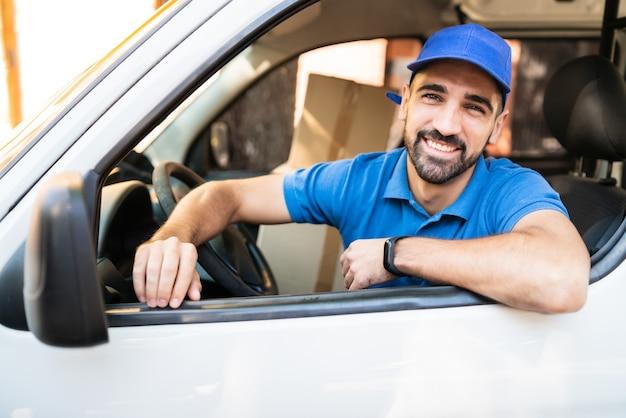 Retrato de un conductor de repartidor conduciendo una furgoneta con cajas de cartón en el asiento. servicio de entrega y concepto de envío.