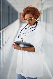 Retrato confía en afroamericana doctora profesional médica escribiendo notas de pacientes aisladas sobre fondo de ventanas de pasillo de clínica de hospital. expresión facial positiva