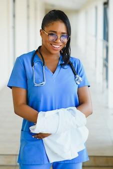 Retrato confía en afroamericana doctora profesional médico escribiendo notas de pacientes aisladas sobre fondo de ventanas de pasillo de clínica de hospital. expresión facial positiva