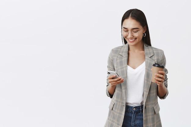 Retrato de confiada empresaria ocupada en gafas y chaqueta, sosteniendo una taza de café y un teléfono inteligente, usando gadget