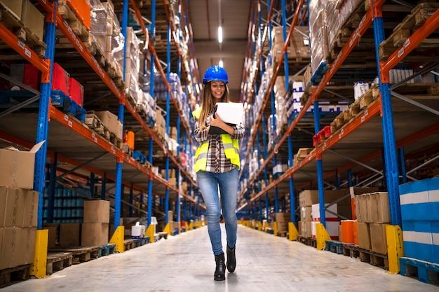Retrato de confiada trabajadora caminando a través del almacén de distribución