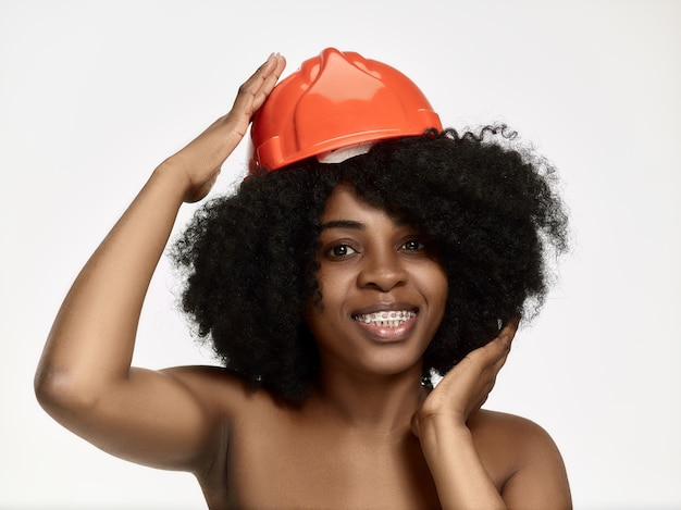 Retrato de confiada trabajadora en casco naranja
