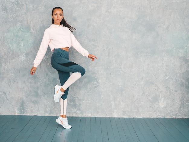 Retrato, de, confiado, condición física, mujer, en, ropa deportiva, mirar confiado., hembra, saltar, en, estudio, cerca, pared gris
