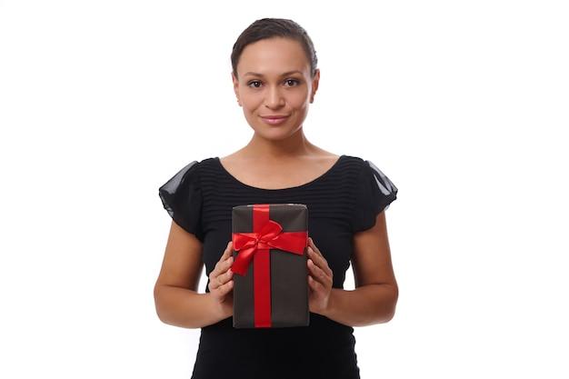 Retrato de confianza aislado sobre fondo blanco de la atractiva hermosa mujer de raza mixta en negro sosteniendo una caja de regalo negra con cinta roja, concepto de viernes negro con espacio de copia