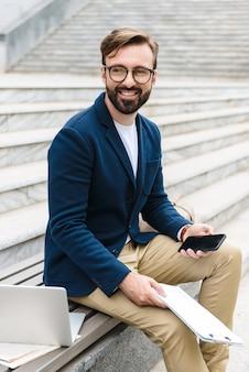 Retrato de confianza empresario con anteojos sosteniendo portapapeles y teléfono celular mientras está sentado en un banco cerca de las escaleras