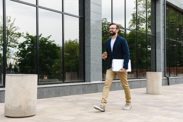 Retrato de confianza empresario con anteojos sosteniendo portátil y vaso de papel mientras camina al aire libre cerca del edificio