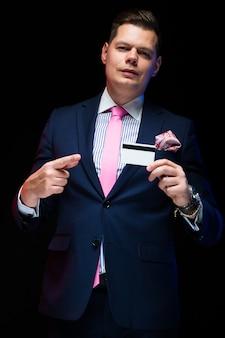 Retrato de confianza empresario elegante guapo con tarjeta de crédito en su mano