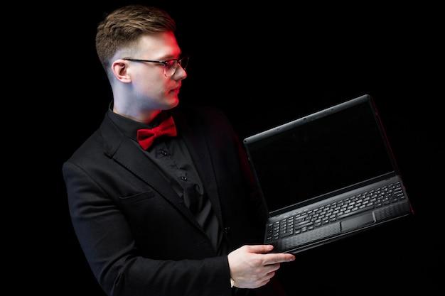 Retrato de confianza guapo ambicioso feliz elegante empresario responsable trabajando en su computadora portátil sobre fondo negro