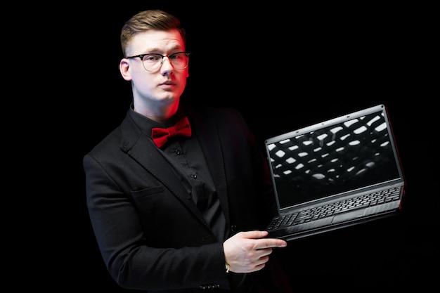 Retrato de confianza guapo ambicioso feliz elegante empresario responsable trabajando en su computadora portátil