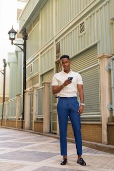 Retrato de confianza joven empresario africano vistiendo ropa casual y mediante teléfono móvil