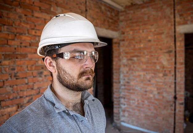 Retrato de un constructor masculino en un sitio de construcción.