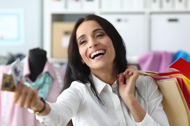 Retrato del consumidor hermoso que mira lejos con alegría y alegría. maravillosa businesslady dando tarjeta de crédito para pagar compras. concepto de compras y moda