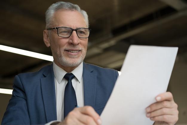 Retrato de contrato de lectura de empresario senior guapo sentado en el lugar de trabajo
