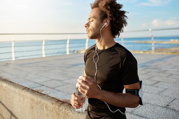 Retrato de corredor afroamericano con los ojos cerrados después del entrenamiento cardiovascular con camiseta negra con auriculares y una botella de agua mineral en las manos. relajarse después de hacer jogging junto al mar