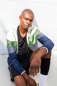 Retrato de un corredor masculino africano joven afeitado grave mirando a la cámara