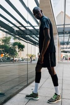 Retrato de un corredor masculino de confianza atleta de pie delante de un vidrio reflectante