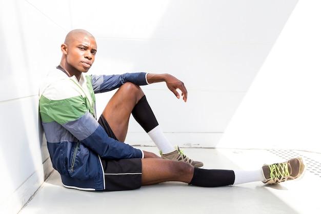 Retrato de un corredor masculino joven que se sienta en la tierra contra la pared blanca que mira la cámara